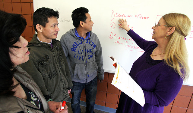 Teacher pointing at whiteboard with three students standing near her.